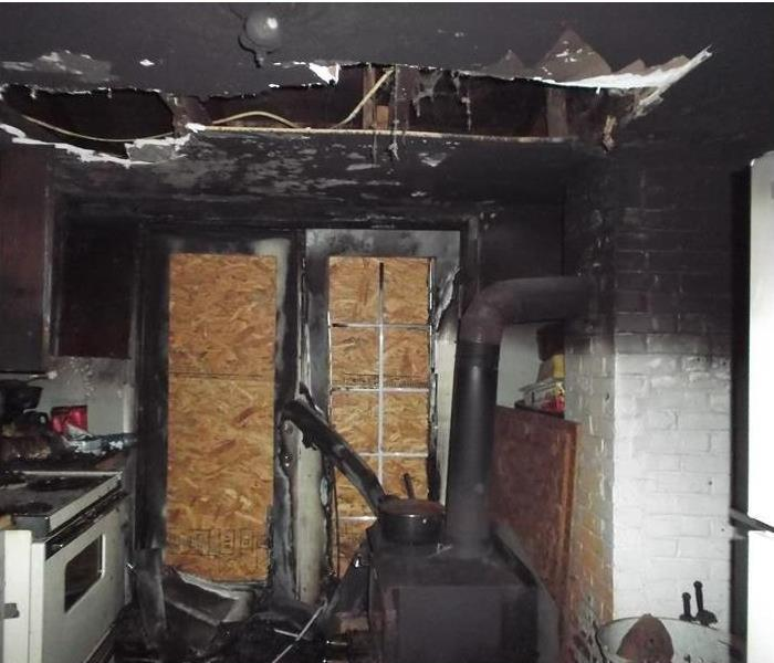 boarded up door passage in a fire damaged kitchen