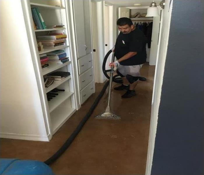 A technician using a cleaning device on the floor after a flood