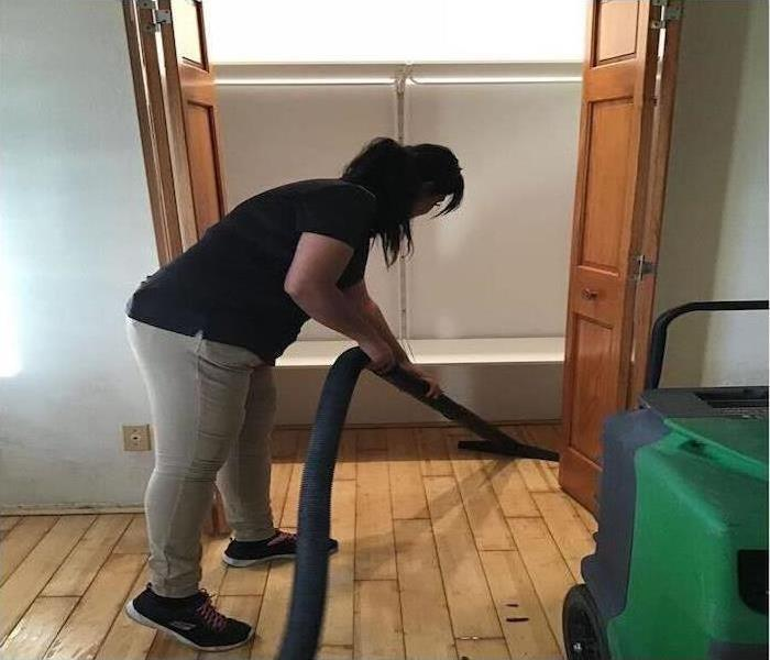one of our technicians cleaning a bedroom of a home after water damage struck